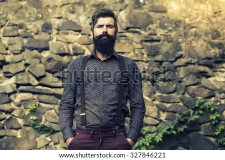 Closeup view of one handsome senior man with black hair and long lush beard in blue shirt and purple trausers standing outdoor on stone wall grey background, horizontal picture - stock photo