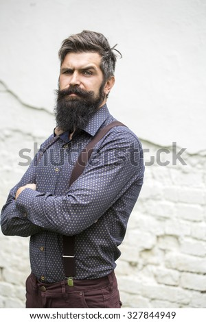 Closeup view of one handsome senior stylish man with black hair and long lush beard in blue shirt standing outdoor on white wall background, vertical picture - stock photo