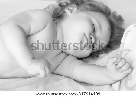 Closeup view of one sweet small sleeping boy child with blonde curly hair round cheeks and tiny fingers lying with closed eyes in bed black and white, horizontal picture