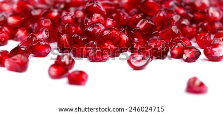 Closeup view of pomegranate seeds on white - stock photo