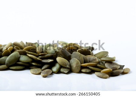 Closeup View of Pumpkin Seeds on a Plain Background - stock photo