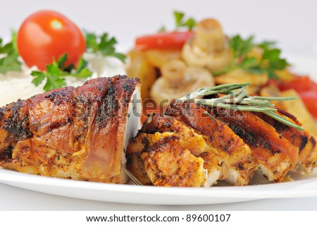 Closeup view of roasted meat served on plate with vegetables - stock photo