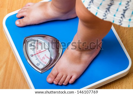 Closeup view of scales on a floor and kids feet - stock photo