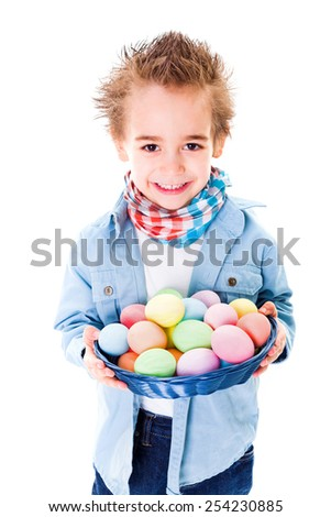 Closeup view of smiling boy showing an basket with colorful Easter eggs - stock photo