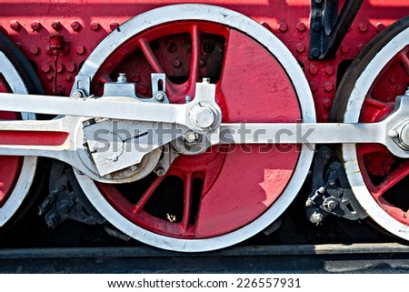 Closeup view of steam locomotive wheels, drives, rods, links and other mechanical details. White, black and red colors. Brakes system. - stock photo