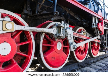 Closeup view of steam locomotive wheels, drives, rods, links and other mechanical details. White, black and red colors