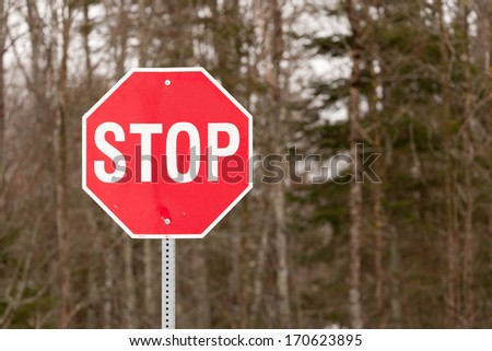 Closeup view of stop sign with trees in background