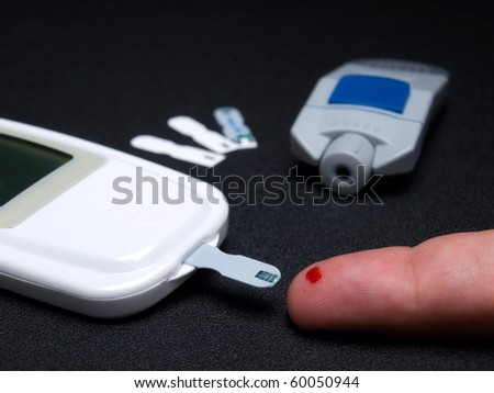 Closeup view of testing of  blood glucose and the necessary equipment. - stock photo