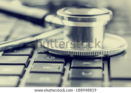 Closeup view of the disc of a stethoscope lying on a laptop keyboard depicting online healthcare and medical advice, retro effect faded look. - stock photo