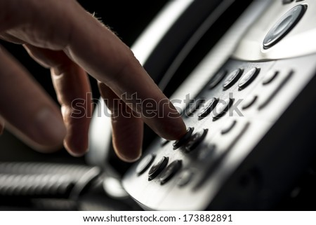Closeup view of the hand of a man making a telephone call on a desktop instrument pressing the numbers on the keypad - stock photo