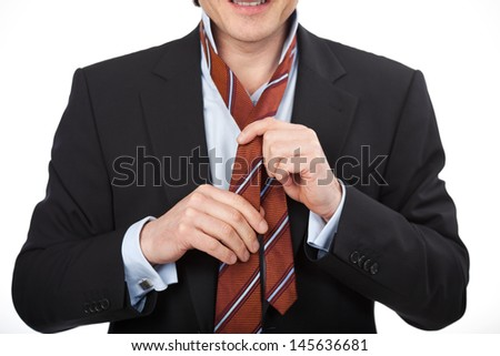 Closeup view of the hands of a man in a suit tying his tie - stock photo