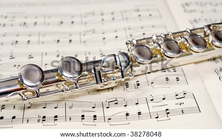 Closeup view of the keys of a metal flute, shot on a music sheet