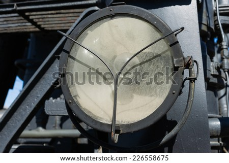 Closeup view of the weathered electrical headlight of a steam locomotive. Electrical bulb inside the cage. Metal constructions and frames in the background - stock photo