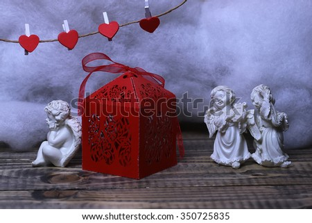 Closeup view of three beautiful cupid angels decorative figurine near red paper greeting valentine box and hanging clothes-peg in shape of heart with white wadding decorating snow, horizontal picture - stock photo