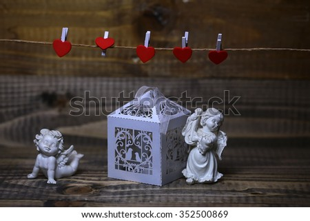 Closeup view of two beautiful cupid angels decorative figurine near white paper greeting valentine box near red clothes-peg in shape of heart with no people on wooden background, horizontal picture - stock photo
