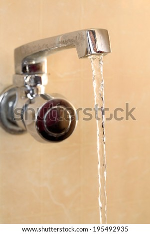 Closeup view of water tap with flowing water - stock photo