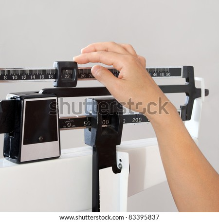 Closeup view of woman's hand adjusting professional balance weight scale. View is closeup, with a neutral background.