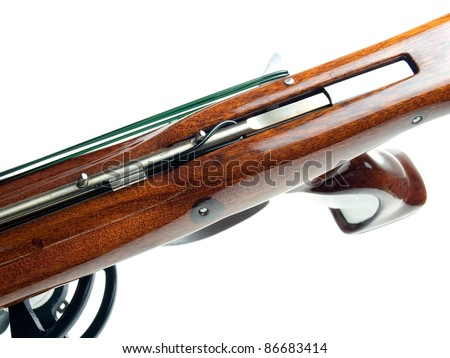 Closeup view of wooden spear gun and trigger mechanism on a white background.