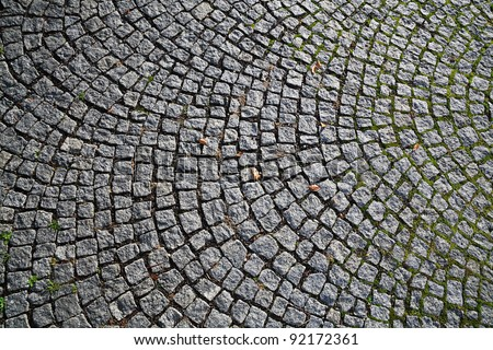 Closeup view on a cobblestone road - pattern - background - contrasty due to a side sunlight - stock photo