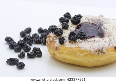 Closeup view on a ring shaped doughnut, fried and glazed with icing, topped with cinnamon powder sprinkles and blueberry jam. Garnished with some dried blueberries. Isolated on white background. - stock photo