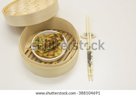 Closeup view on fried beat egg and garlic chives mixture to thin sheet and wrap over fish paste. Serve in eating Chinese dim sum setting with bamboo  basket and a pair of chopsticks. White background. - stock photo