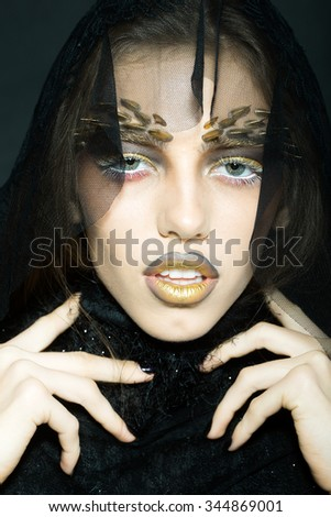 Closeup view portrait of one attractive sensual wild young woman with bright golden animal makeup with thorns on face in lace veil in studio on black background, vertical picture