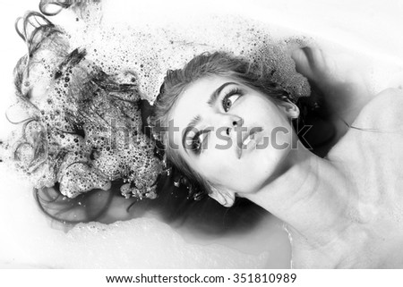 Closeup view portrait of one beautiful sensual smiling young woman with wet hair and bright makeup lying in bath tub with water and white soap foam looking away, horizontal picture - stock photo