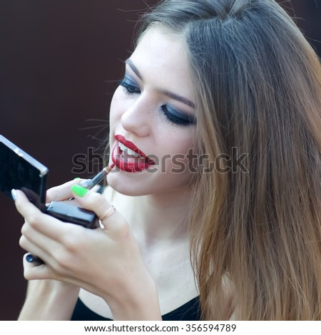Closeup view portrait of one fashionable pretty young sensual woman with long lush hair and bright makeup holding mirror and putting on red lipstick on mouth outdoor, square picture