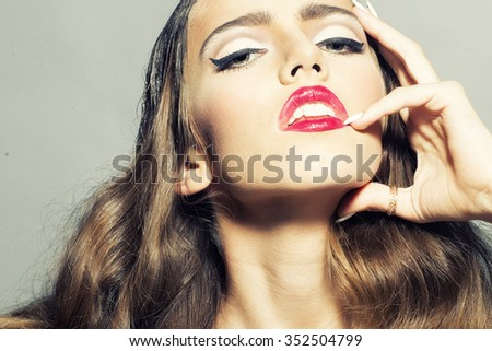 Closeup view portrait of one glamour fashionable sexy pretty young stylish woman with beautiful curly long hair and bright red lips and makeup looking forward in studio, horizontal picture - stock photo