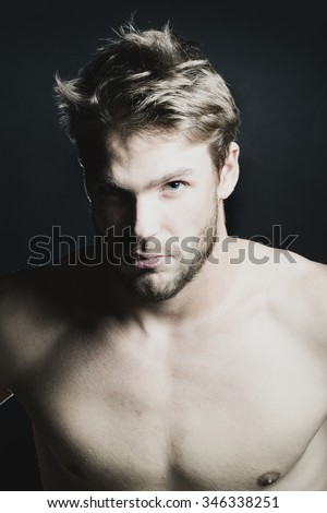 Closeup view portrait of one handsome young muscular naked sexy macho man with short hair bare chest and beautiful body standing in studio on black backdrop, vertical picture - stock photo
