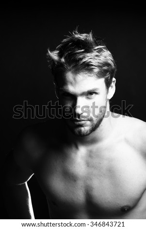 Closeup view portrait of one handsome young muscular naked sexy macho man with short hair bare chest and beautiful body standing in studio black and white, vertical picture - stock photo