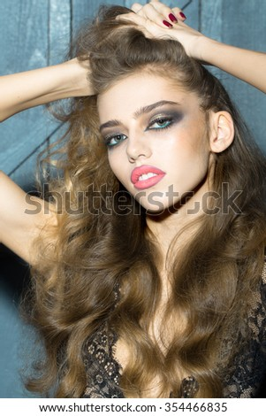 Closeup view portrait of one pensive attractive sexual sensual young fashionable woman holding long curly hair with hands with bright makeup on wooden background, vertical picture