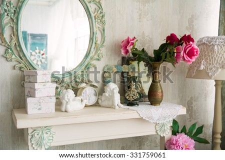 Closeup vintage interior with mirror and a table with a vase and flovers. Designer wall clock. Angels on the table