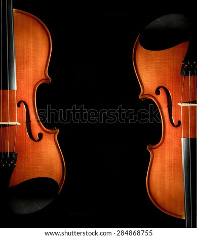 Closeup Violin orchestra musical instruments on black background - stock photo