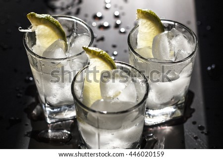 Closeup vodka in a glass with ice, lime.  Gin, tonic, tequila - stock photo