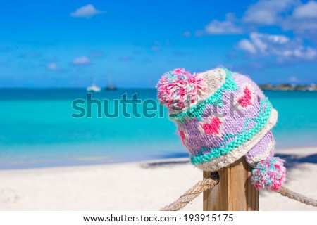 Closeup warm knitted cap on fence at tropical beach - stock photo