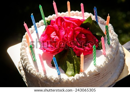 closeup white creamy delicious cake decorated with candles  and three red roses on the top  - stock photo
