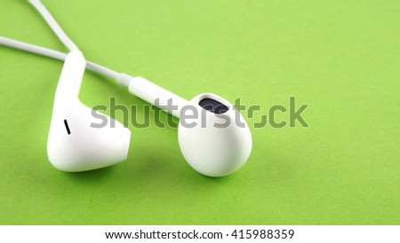 Closeup, white earphones on a green background - stock photo