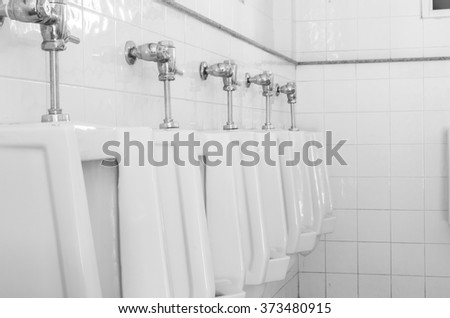 Closeup  white urinals in men's bathroom, design of white ceramic urinals for men in toilet room - stock photo