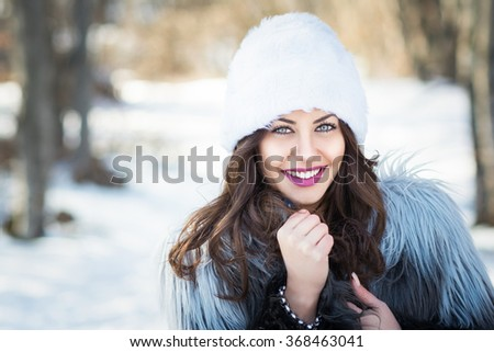 Closeup winter portrait of gorgeous happy young brunette woman in fur hat and coat. Young female model wearing makeup posing outdoors on snowy winter day. Retouched, horizontal, copy space. - stock photo