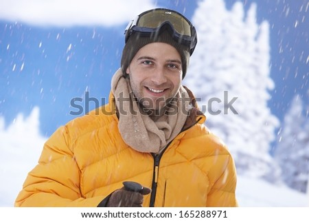 Closeup winter portrait of happy young male skier.