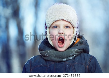 Closeup winter portrait of young shouting boy in hat, scarf and jacket at outdoors background. - stock photo