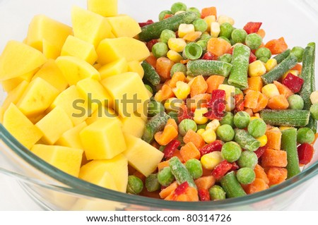 Closeup with potatoes and frozen mixed vegetables - stock photo