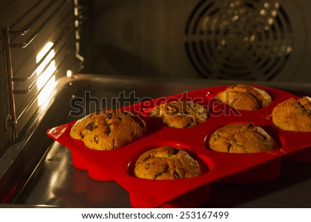 closeup with selective focus of home-made muffins cake in electric oven - stock photo