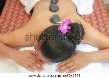 Closeup woman and orchid  receiving hot stone massage at spa salon,