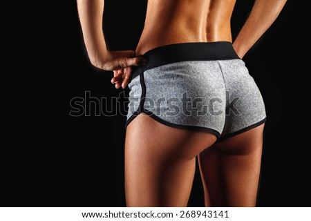 closeup woman beautiful buttocks over dark background - stock photo