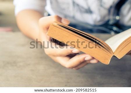 Closeup woman hand  holding pocket book to read - stock photo