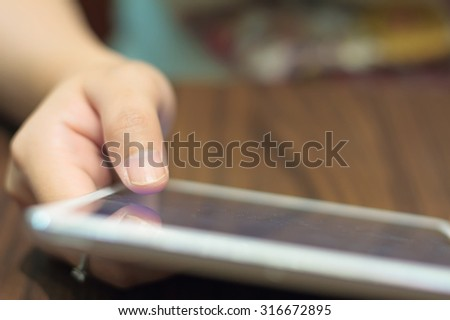 closeup woman hands using tablet computer on wooden table