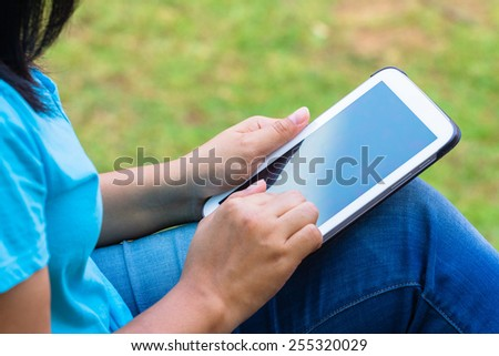 Closeup woman in casual cloths using computer tablet in the park