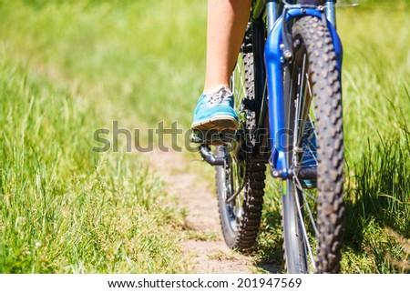 Closeup  woman riding mountain bike outdoors. - stock photo